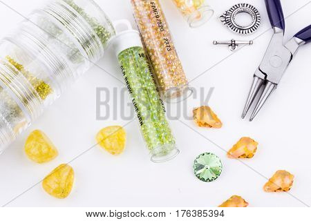 Jewelry making and beading process. Glass seed beads beads crystal stones silver toggle jewelry bag and pliers on white background. Selective focus.