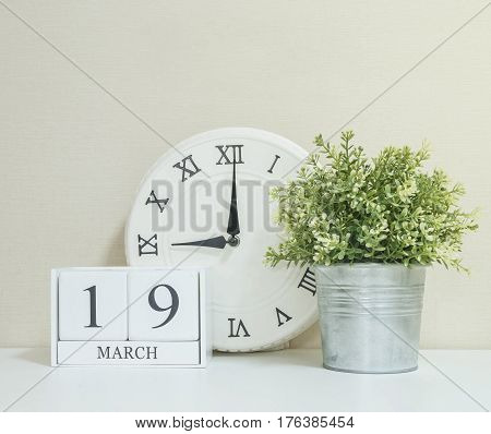 White wooden calendar with black 19 march word with clock and plant on white wood desk and cream wallpaper textured background selective focus at the calendar