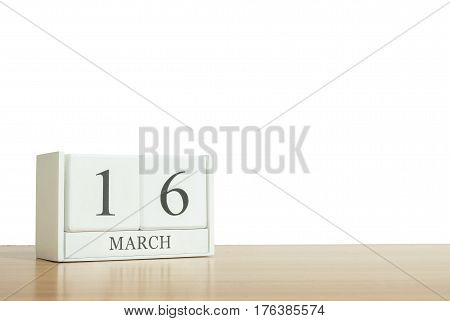 Closeup surface white wooden calendar with black 16 march word on blurred brown wood desk isolated on white background with copy space selective focus at the calendar