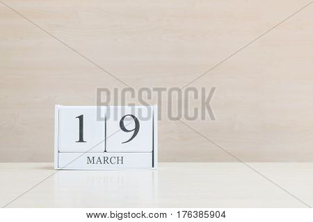 Closeup surface white wooden calendar with black 19 march word on blurred brown wood desk and wood wall textured background with copy space selective focus at the calendar