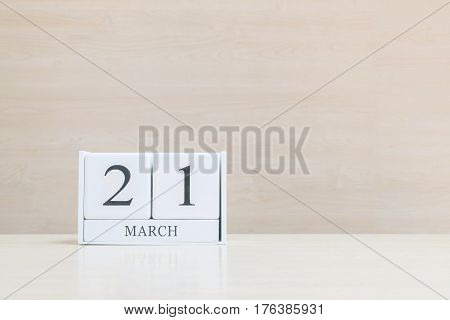 Closeup surface white wooden calendar with black 21 march word on blurred brown wood desk and wood wall textured background with copy space selective focus at the calendar