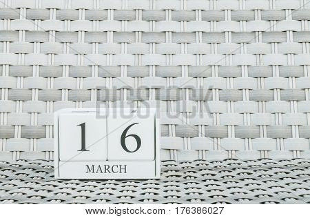 Closeup surface white wooden calendar with black 16 march word on blurred weave wood chair textured background with copy space selective focus at the calendar