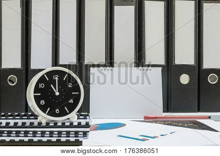 Closeup white clock for decorate in 11 o'clock desk of officer with work paper and document file in office room textured background in work concept