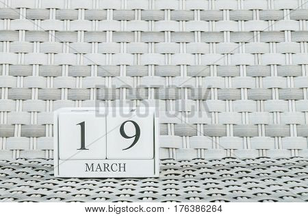 Closeup surface white wooden calendar with black 19 march word on blurred weave wood chair textured background with copy space selective focus at the calendar