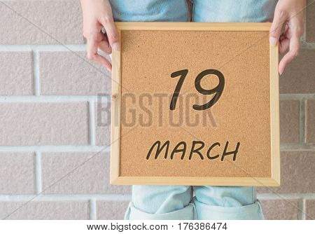 Closeup calendar at the cork board in hand of asian woman in front of her legs with 19 march word on brick wall textured background