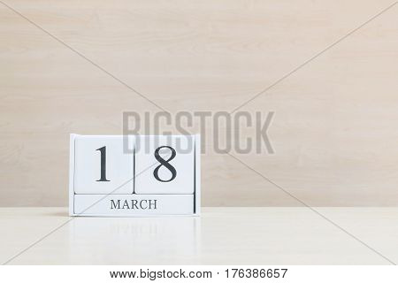 Closeup surface white wooden calendar with black 18 march word on blurred brown wood desk and wood wall textured background with copy space selective focus at the calendar
