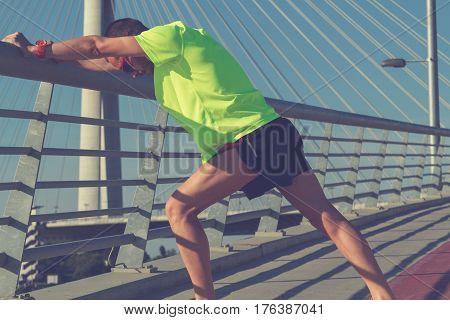 Slim urban jogger stretching on the bridge.