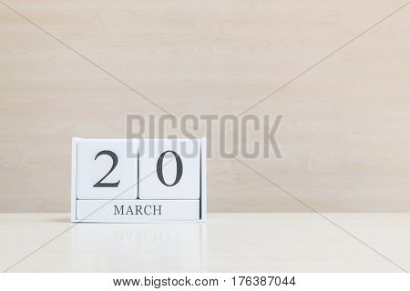 Closeup surface white wooden calendar with black 20 march word on blurred brown wood desk and wood wall textured background with copy space selective focus at the calendar