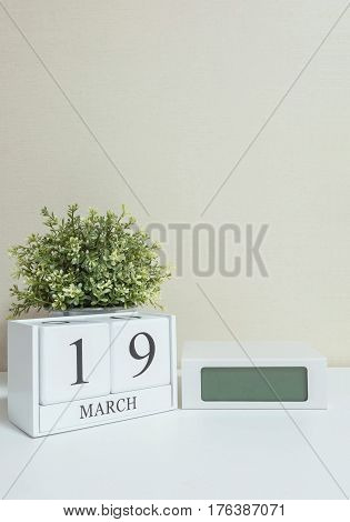 White wooden calendar with black 19 march word with clock and plant on white wood desk and cream wallpaper textured background in selective focus at the calendar