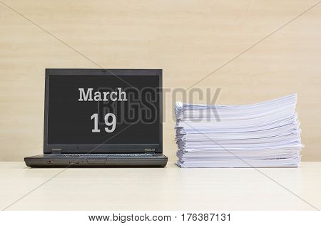 Closeup computer laptop with march 19 word on the center of screen in calendar concept and pile of work paper on wood desk and wood wall in work room textured background with copy space