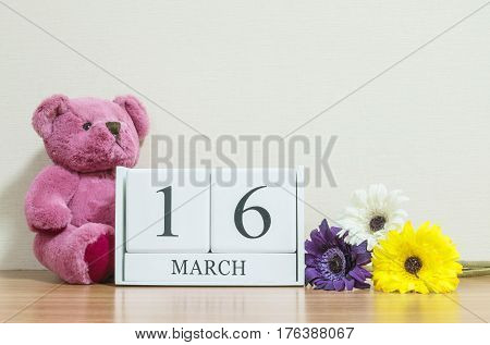Closeup surface white wooden calendar with black 16 march word on brown wood desk and cream color wallpaper in room textured background with copy space selective focus at the calendar