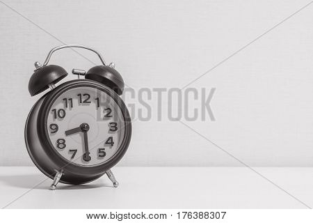 Closeup alarm clock for decorate show half past eight or 8:30 a.m.on white wood desk and cream wallpaper textured background in black and white tone with copy space