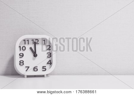 Closeup white clock for decorate in 11 o'clock on white wood desk and cream wallpaper textured background in black and white tone with copy space