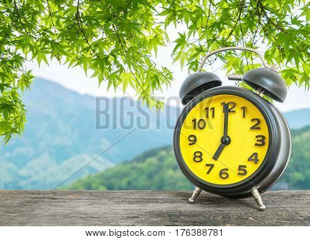 Closeup black and yellow alarm clock for decorate in 7 o'clock on blurred leaves and mountain view background