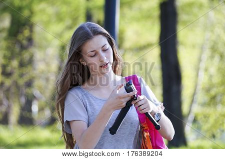 young girl in the Park shooting with an action camera, the joy of life, positive emotions, love of nature