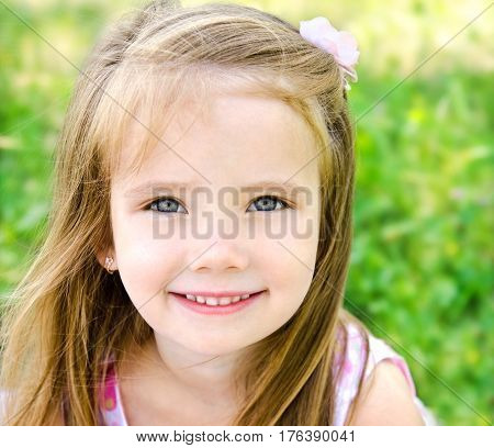 Adorable smiling little girl on the meadow in summer day outdoors