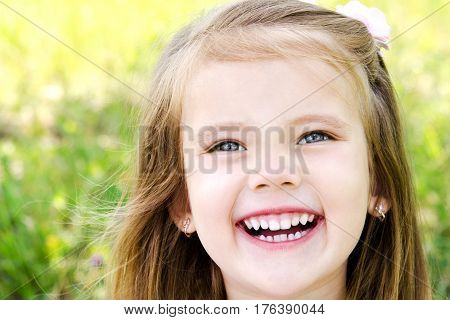 Portrait of happy little girl on the meadow in summer day