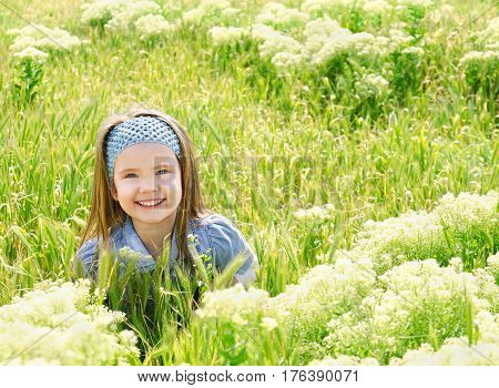 Happy smiling little girl on the meadow in summer day