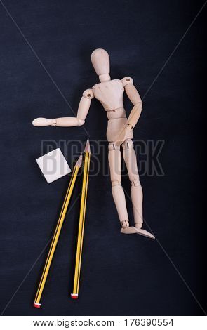 Wooden puppet for learning to draw on a black wooden board