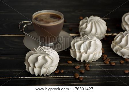 White zephyr with cup of coffee on dark wooden background