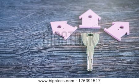 Silver Key surrounded Sign of Lilac Houses on Dark Wooden Surface.