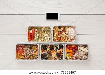 Internet order of healthy restaurant food, mockup background. Fresh diet daily meals delivery. Vegetables, seafood, meat and fruits in foil box. Top view, flat lay on wood, copy space