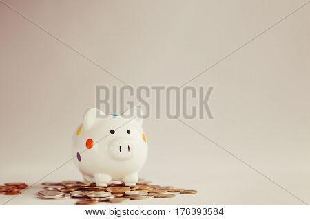 White piggy bank or money box standing on heap of money coins