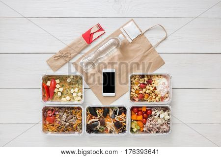 Mockup for online order, daily meals delivery background. Fresh diet food. Vegetables, seafood, meat and fruits in foil box. Top view, flat lay on wood, copy space