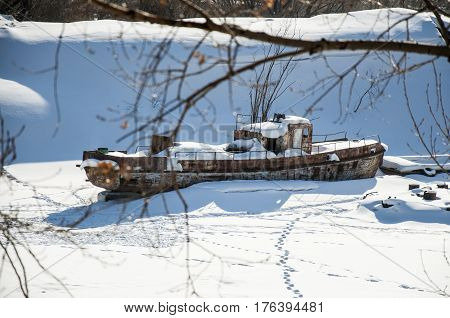 The old riverboat is frozen on the ice