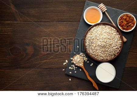 Oat Flakes In The Bowl And Honey, Raisins, Milk On Slate Board And Rustic Wooden Background.