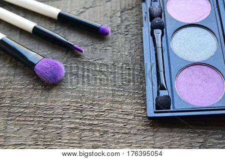 Makeup brushes and eye shadow palette on old wooden background with copy space.Various make-up products.Fashion cosmetic makeup or woman beauty accessories concept.Selective focus.