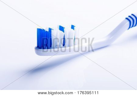 Toothbrush isolated on a white background with reflection. Blue plastic toothbrush. Concept of medicine.