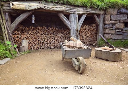 Old vintage wooden cart and firewood stockpile