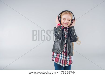Adorable Smiling Girl With Closed Eyes Wearing Headphones On Grey