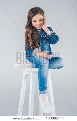 Cute Smiling Little Girl Sitting On Stool And Talking On Smartphone