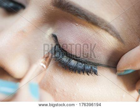 Closeup Of Woman Applying Eyeliner