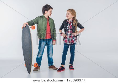 Confident Smiling Boy And Girl Standing With Skateboard And Looking At Each Other