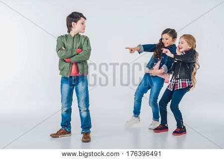 Girls Making Fun Of Proud Boy And Pointing With Fingers On Grey