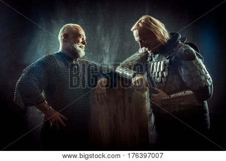 Two Powerful Knights Resting In The Tavern. Dark Background.