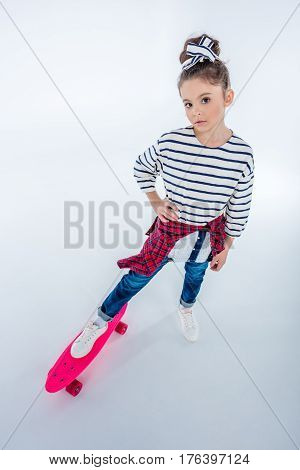 High Angle View Of Serious Girl Standing With Skateboard On Grey