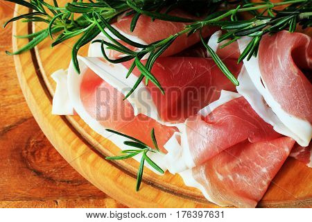 slices of ham and rosemary on a cutting board