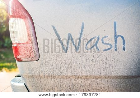 Written text Wash Now on dorr of dirty car