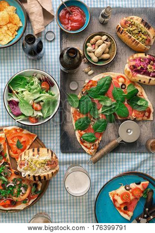 Italian pizza hot dog grilled salad lager and snacks to beer top view. Dinner table with various delicious food top view rustic style
