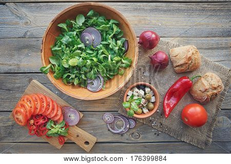 Ingredients for vegetables salad on a wooden background: lettuce leaves tomatoes red pepper onions olives oil and cheese. Top view.