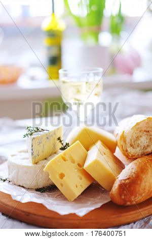 Cheese plate with different kinds of cheese with a glass of white wine and baguette
