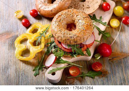 Vegetarian bagel sandwich with fresh veggies and arugula salad vegan healthy food lunch breakfast picknick snack