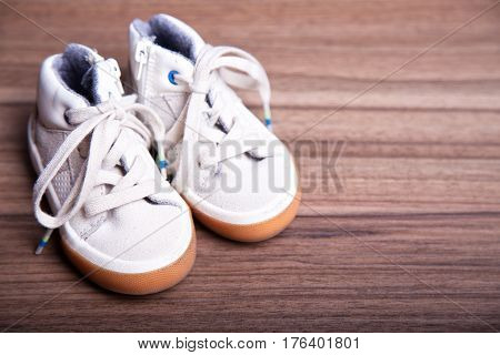 children's shoes on wooden background with place for text. first shoes baby