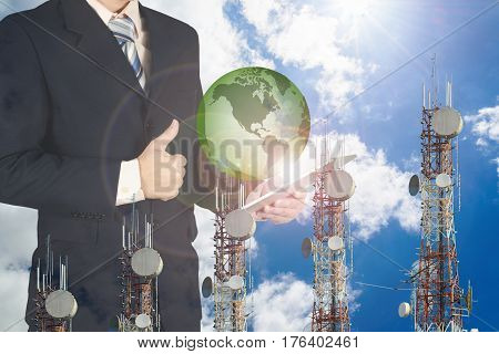 Double Exposure Of Businessman Using Tablet With Green Earth Planet And Give Thumbs Up On Blue Sky A