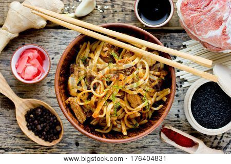 Udon noodles with meat in sauce and ingredients on a wooden table traditional Asian cuisine top view