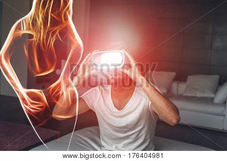 Young man with VR headset playing with fiery sexy woman silhouette virtual reality